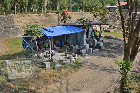 pekerja memotong batu pemugaran candi kedulan