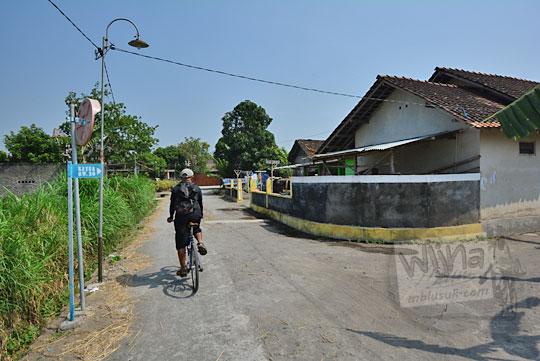 seorang pria bersepeda di jalan dusun segaran desa tirtomartani kalasan sleman yogyakarta yang masih asri banyak sawah pada zaman dulu