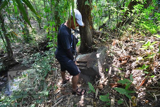 seorang pria sedang mengamati batu candi besar di dusun segaran tirtomartani kalasan sleman yang disebut oleh warga setempat sebagai watu gilang atau batu singgasana