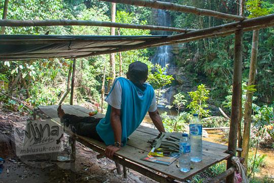 foto pria duduk bersantai di salah satu gubuk objek wisata alam air terjun panisan di desa tanjung kecamatan koto kampar hulu riau pada zaman dulu April 2016