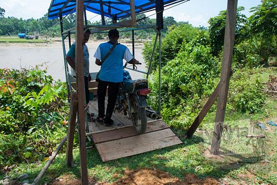 foto sepeda motor naik gondola sungai kampar kanan