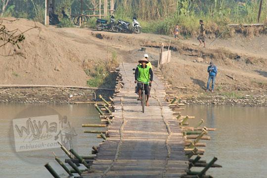 seorang bapak naik sepeda melintasi jembatan bambu sesek lendah