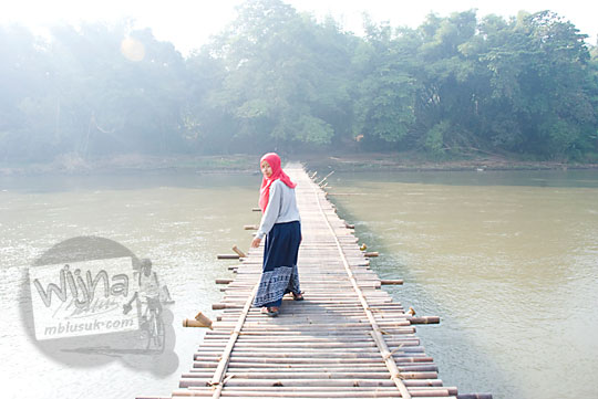 wanita berjilbab berjalan kaki melintasi jembatan bambu sesek jogja