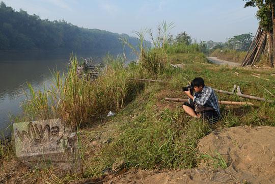 gaya seorang pria memotret dengan duduk di semak-semak