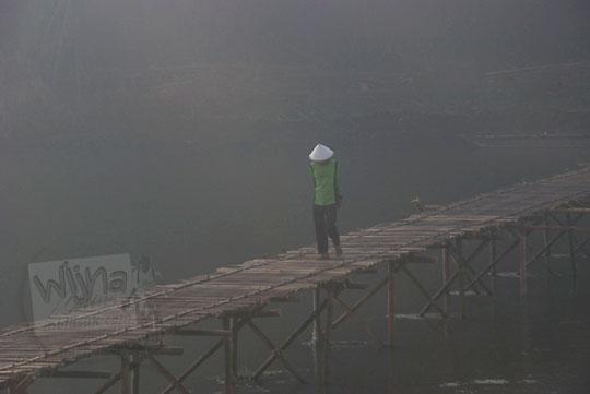 foto pria berjalan kaki di jembatan bambu sesek mangir