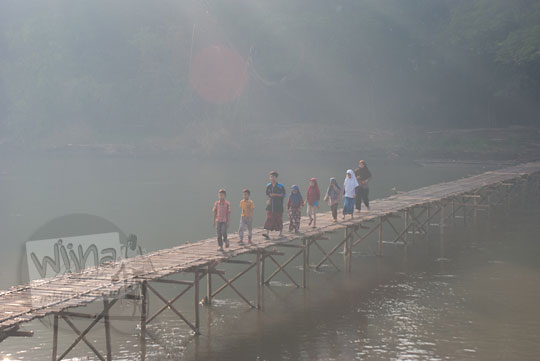 rombongan anak berjalan kaki melewati jembatan bambu sesek mangir