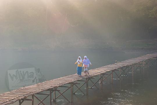 dua orang gadis bergandengan tangan berjalan kaki melewati jembatan bambu sesek mangir