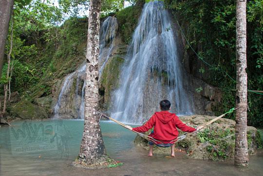 pria duduk di air terjun randusari