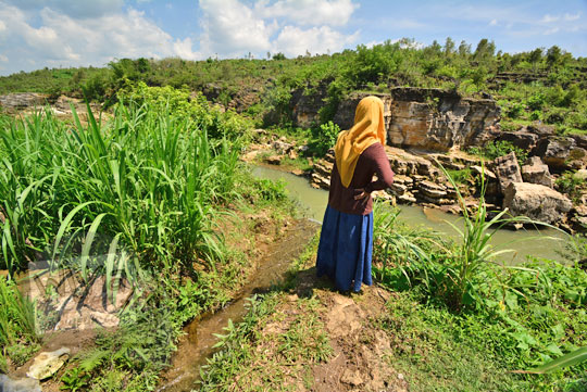 wanita berdiri di puncak air terjun curug ngembel yang masuk desa karangtengah wonosari gunungkidul