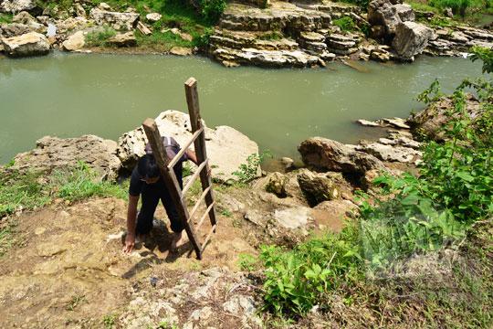 pria memanggul tangga menuruni tebing lembah sungai oya di desa karangtengah wonosari gunungkidul