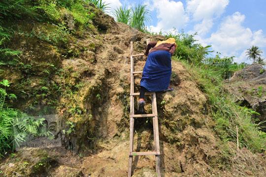 wanita menuruni tangga lembah tebing sungai oya di desa karangtengah wonosari gunungkidul