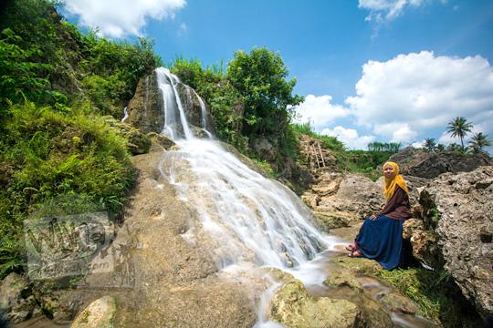 wanita cantik duduk di dasar air terjun curug ngembel di desa karangtengah wonosari gunungkidul