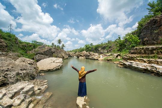 wanita berdiri di batu di dasar lembah sungai oya di desa karangtengah wonosari gunungkidul