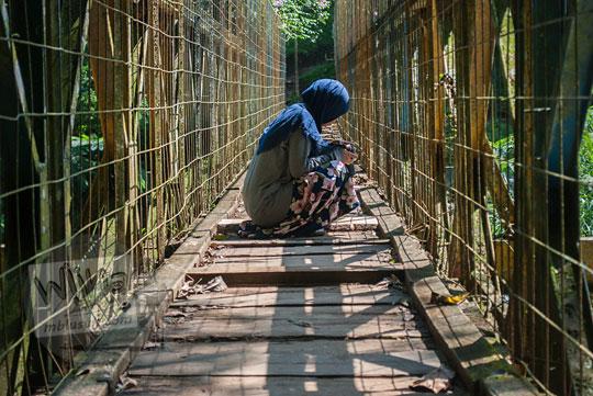 wanita jongkok sedang memotret jembatan curug omas maribaya