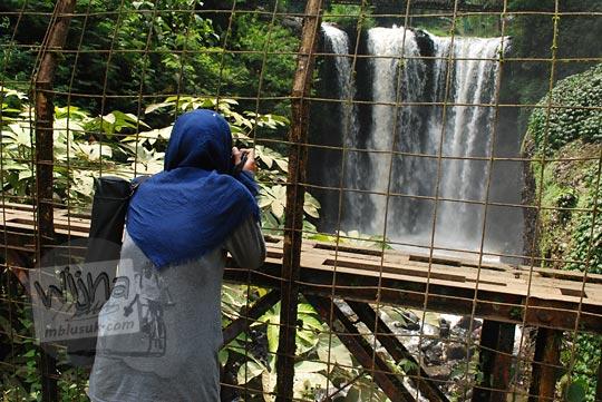 wanita berdiri sedang memotret jembatan curug omas maribaya