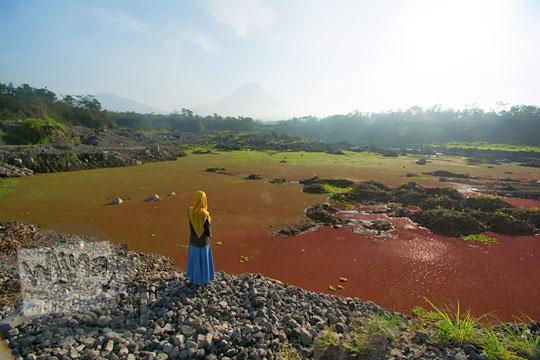 perempuan berdiri di muka telaga merah gunung merapi magelang