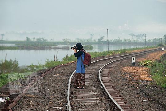 wanita memotret rel kereta mati rawa pening