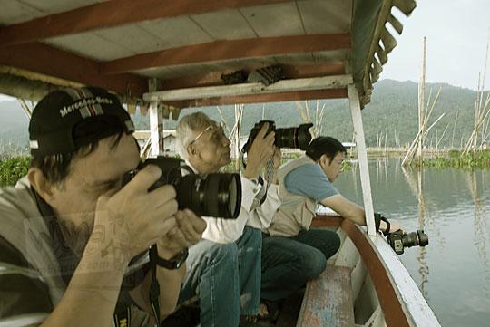 fotografer memotrer naik perahu rawa pening
