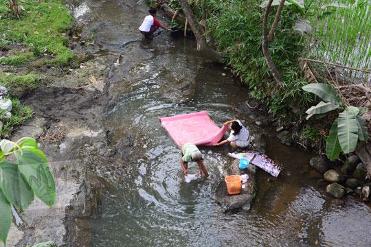ibu-ibu warga desa mencuci baju di sungai klaten