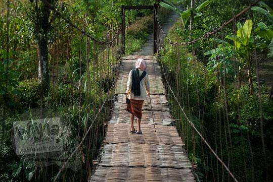 nenek bertongkat menyeberangi jembatan gantung kalisemo mudalrejo di Purworejo Jawa Tengah
