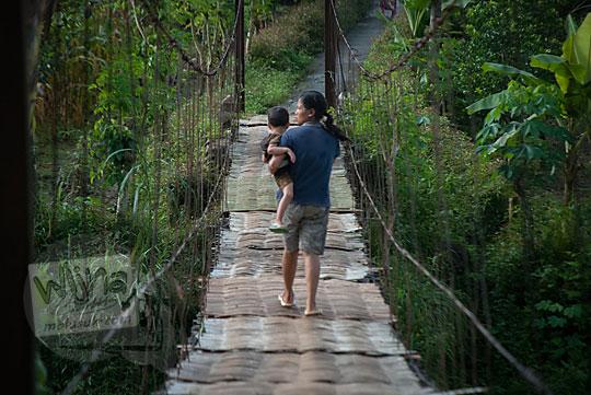 foto seorang wanita menggendong anak menyeberangi jembatan gantung kalisemo mudalrejo di Purworejo Jawa Tengah