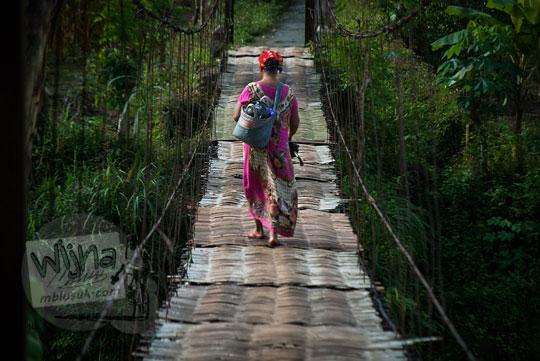 foto seorang ibu pedagang pasar menyeberangi jembatan gantung kalisemo mudalrejo di Purworejo Jawa Tengah