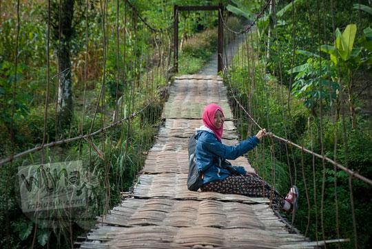 wanita berjilbab duduk di lantai jembatan gantung kalisemo mudalrejo di Purworejo Jawa Tengah