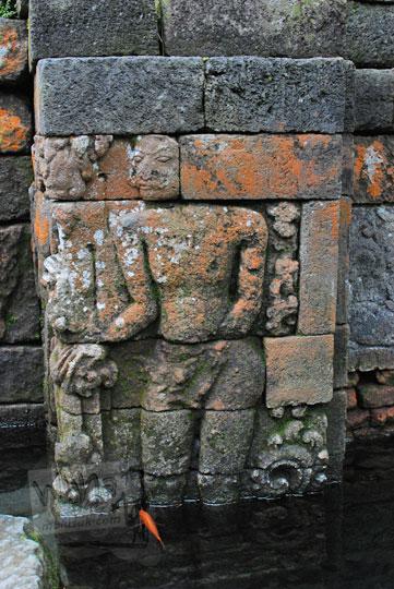 relief sosok pria di dinding kolam pertirtaan candi penataran