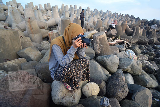 wanita memotret di hamparan tetrapod pantai glagah kulon progo yogyakarta