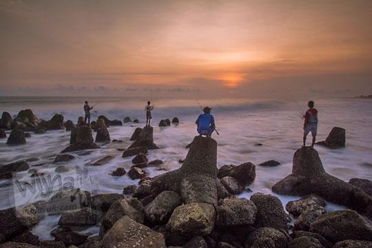 bapak-bapak pemancing berlatar senja di pemecah ombak pantai glagah kulon progo yogyakarta