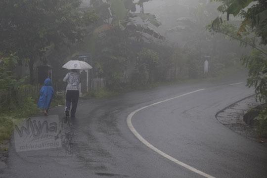 orang berjalan kaki di jalan aspal tertutup kabut di dusun plono timur samigaluh kulon progo
