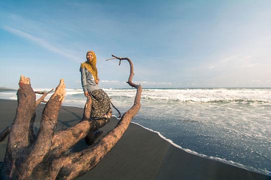 wanita duduk di bangkai pohon pantai bugel kulon progo