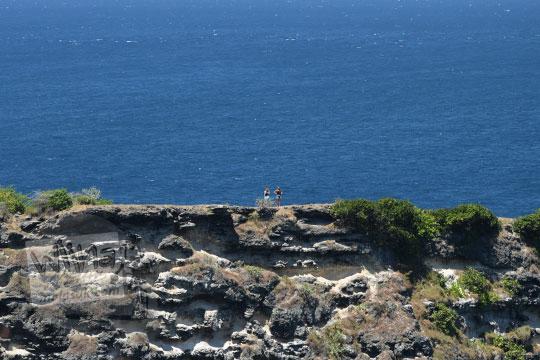 pasangan turis asing berfoto di salah satu tebing tanjung ringgit