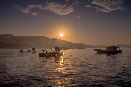 pemandangan matahari terbit dilihat dari dermaga rakyat pantai kuta lombok