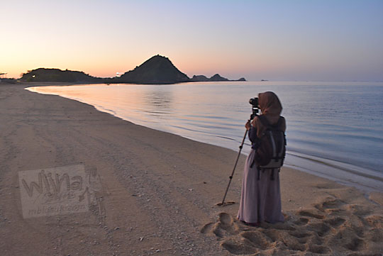 wanita memotret sunrise pantai kuta lombok
