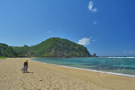 wanita berjilbab berjalan kaki menyusuri pantai nambung lombok