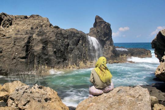 wanita duduk menunggu air terjun di pantai nambung
