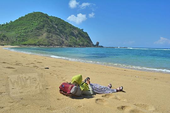 wanita tiduran di hamparan pasir pantai nambung