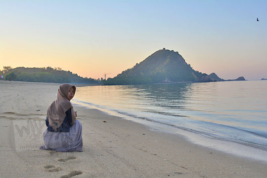 wanita memotret sunrise pantai kuta mandalika