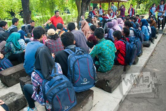 sekelompok mahasiswa sedang mendengarkan ceramah dari juru pelihara candi sambisari tentang perawatan benda purbakala