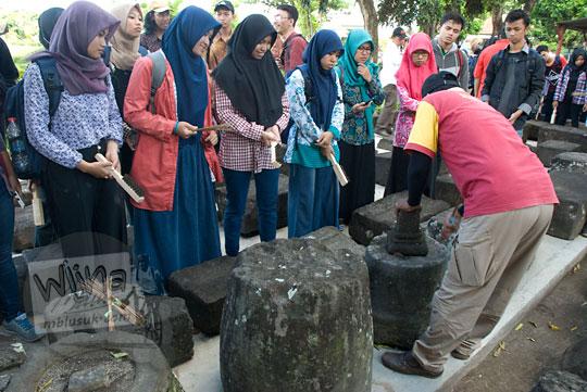 sejumlah mahasiswi sejarah mendengarkan penjelasan cara merawat batu candi sambisari oleh bapak juru pelihara