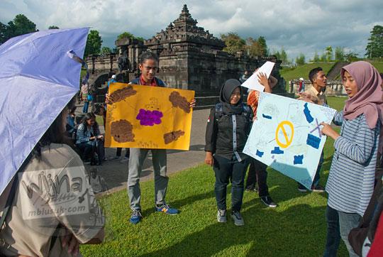 sejumlah mahasiswa sedang menjelaskan pelestarian dan perawatan benda cagar budaya kepada pengunjung candi sambisari