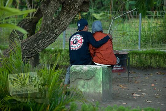 pasangan anak muda berpacaran mesra di bangku taman candi sambisari
