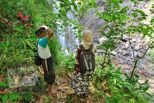 warga desa donorejo bernama bapak paidi menjelaskan ke turis perihal sejarah air terjun kembar mayang atau curug ngedok di kaligesing purworejo