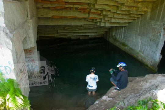 dua pria jongkok di muka kolam gua permoni