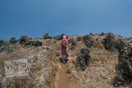 wanita mendaki bukit karang pantai kasap pacitan