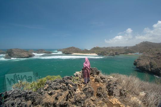 wanita berdiri puncak bukit karang pantai kasap pacitan