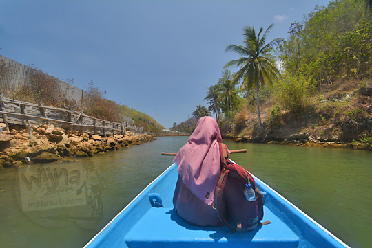 wanita duduk perahu susur sungai cokel pacitan