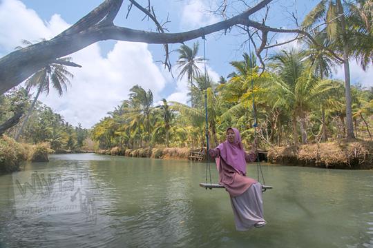 wanita berfoto naik ayunan sungai cokel pacitan