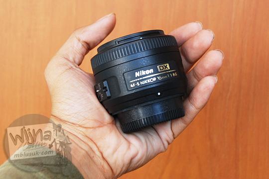 perbandingan ukuran lensa AF-S DX Nikkor 35mm dengan tangan orang dewasa